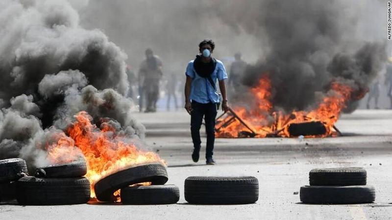 A Nicaraguan protester walks among burning barricades during political unrest in Managua this summer.