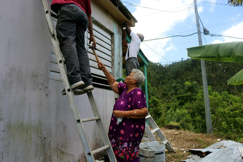 Gregoria lends a hand to one of the men fixing the roof of her home in Trujilo Alto. After Hurricane Maria destroyed her roof, Gregoria had only a blue tarp protecting her home for almost a year.