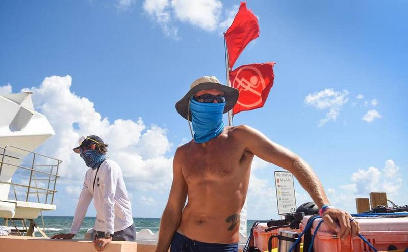 Palm Beach lifeguards Ryan Zabovnik, left, and George Klein wear masks at Midtown Beach in Palm Beach that remains closed due to red tide warnings, Sunday, September 30, 2018.