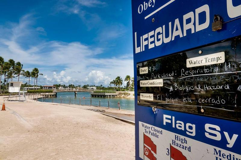 A lifeguard sign warns visitors of closed water due to biological and respiratory hazards at Dubois Park in Jupiter on Monday. The state confirmed it was red tide.