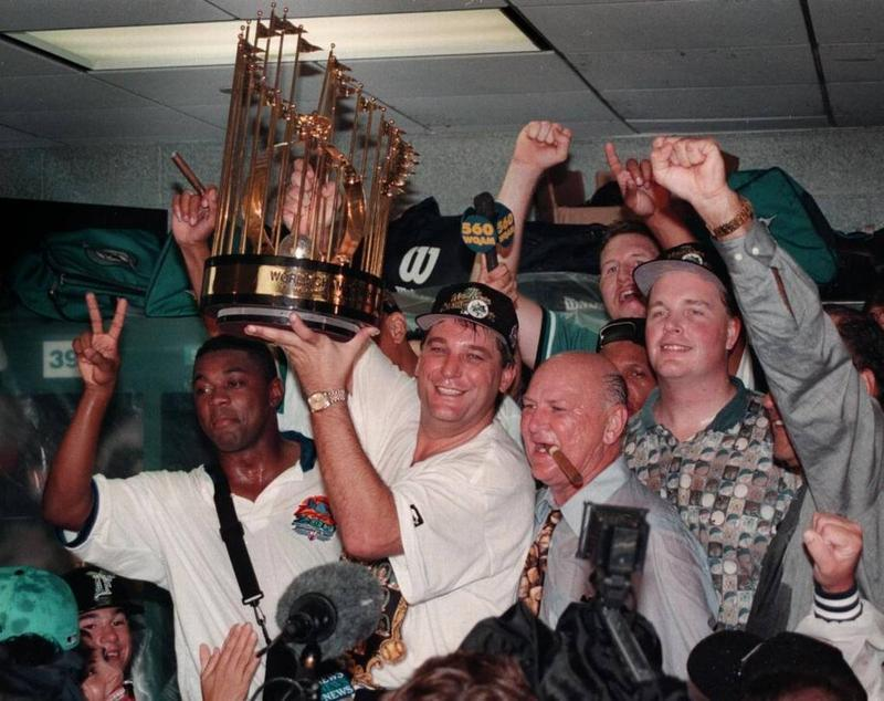 Don Smiley hoists the championship trophy in the Marlins locker room after the Marlins defeated the Cleveland Indians in Game 7 of the 1997 World Series. To his right with a cigar in his mouth is club owner H. Wayne Huizenga.