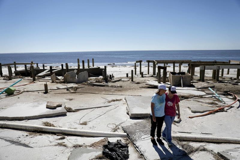 Joy Hutchinson, left, is comforted by her daughter Jessica Hutchinson, as she returns to find her home swept away from hurricane Michael in Mexico Beach, Fla. It was once argued that the trees would help save Florida's Panhandle from hurricanes.