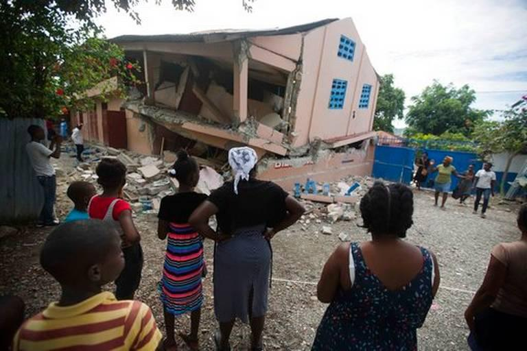 Residents stand looking at a collapsed school damaged by a magnitude 5.9 earthquake the night before, in Gros Morne, Haiti, Sunday, Oct. 7, 2018.