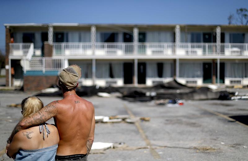 Residents line up for food from the Red Cross outside a damaged motel, Tuesday, Oct. 16, 2018, in Panama City, Fla., where many residents continue to live in the aftermath of Hurricane Michael. Some residents rode out the storm and have no place to go.
