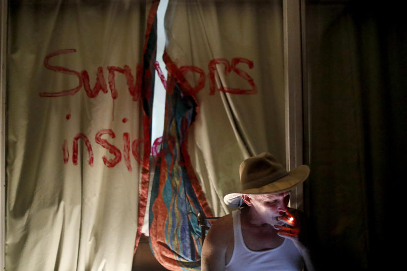 """Wes Allen, Sr., smokes a cigarette outside his room at the damaged American Quality Lodge as the message """"Survivors inside"""" is written on the window in the aftermath of Hurricane Michael, in Panama City, Fla., Tuesday, Oct. 16, 2018."""