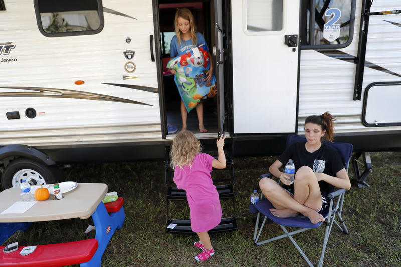 Kahlan Ladik, 14, sits next to the camper her family just bought as temporary housing, since their home was heavily damaged by Hurricane Michael in Panama City, Fla., Wednesday, Oct. 17, 2018. With her are her siblings Madison, 3, and Lilly, 6, top.