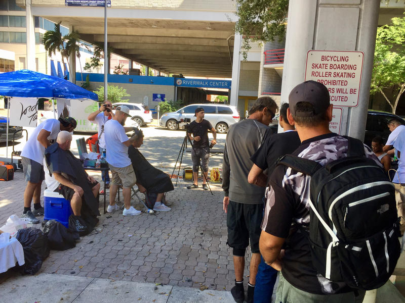 Homeless people wait in line for a free haircut.