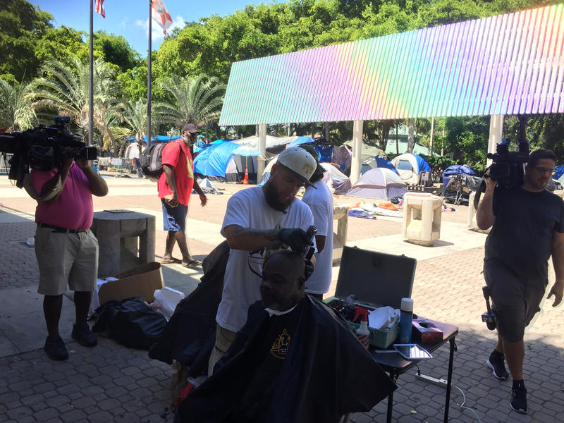 Greg Young, founder of the Backpack Barber, and local barbers, give free haircuts to the homeless outside of tent city in Fort Lauderdale, Oct. 1, 2018.