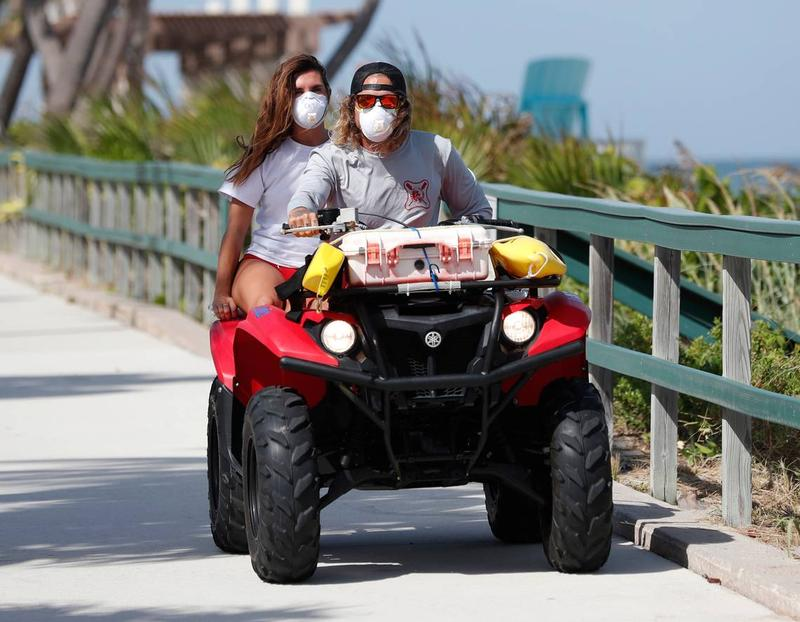 Palm Beach County Ocean Rescue workers wear masks as they ride an all terrain vehicle along Lake Worth Beach on Tuesday.