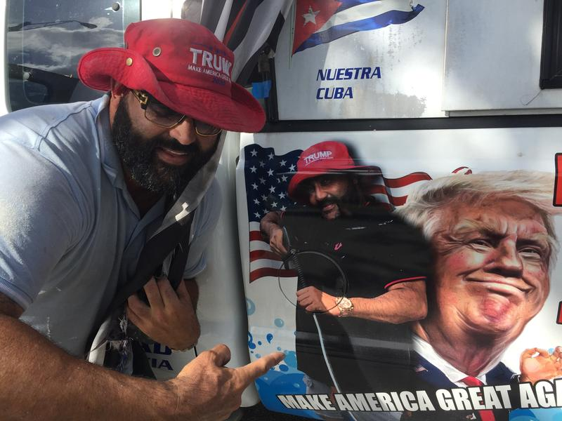 Conservative Cuban-American voter Alberto Hernandez shows off the picture of President Trump on his painting company's pickup truck in Kendall on Tuesday.