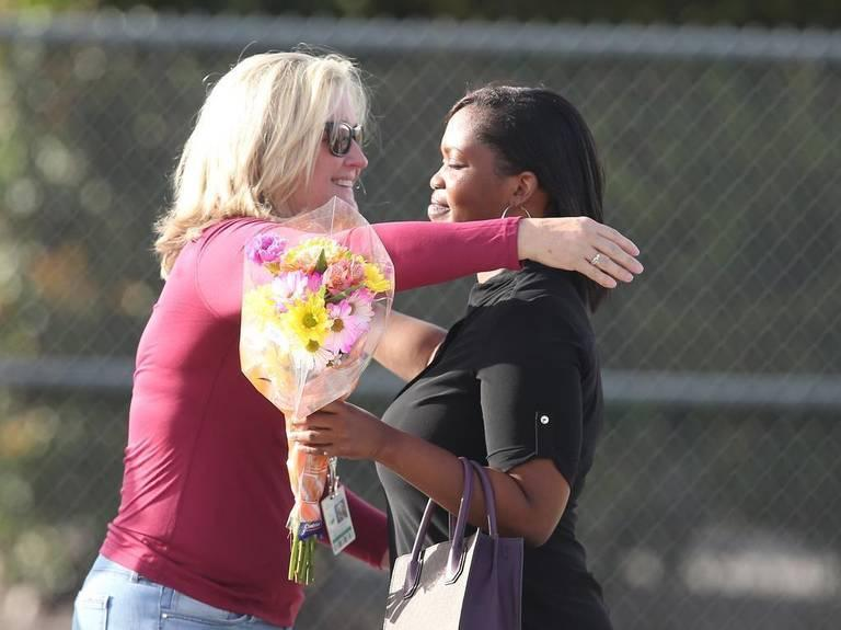 Marjory Stoneman Douglas High Assistant Principal Denise Reed hugs a school employee as she returns to campus with flowers on Feb. 23, 2018, following the mass shooting. Reed is among four school employees who are being reassigned.