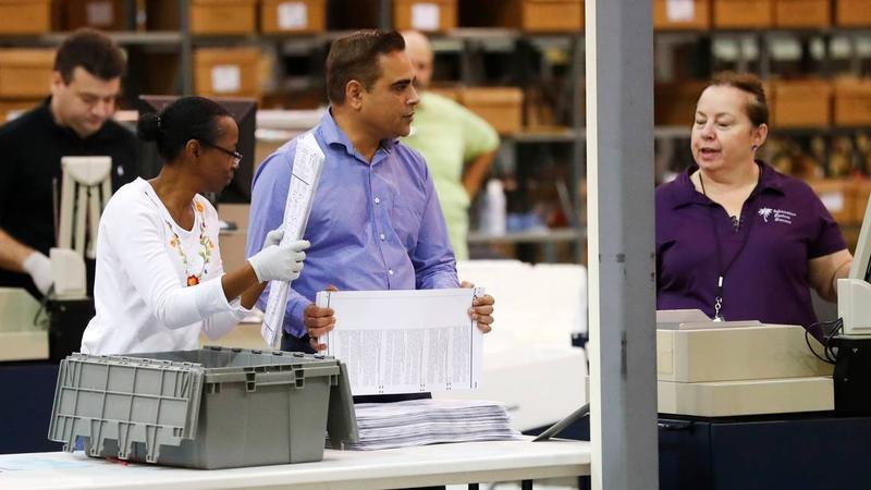 Employees at the Palm Beach County Supervisor of Elections office feed ballots through a machine Tuesday during the ongoing recount as they race to make a Thursday deadline.