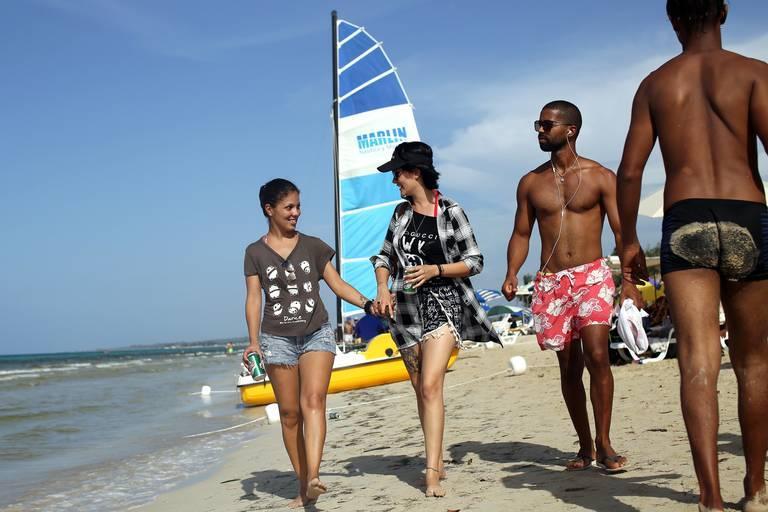 A Cuban lesbian couple stroll a beach near Havana.