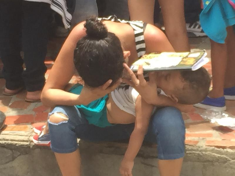 WORST HUMANITARIAN CRISIS: An exhausted Venezuelan refugee tries to give her toddler son shade while waiting for food stamps in Cucuta, Colombia, this year.