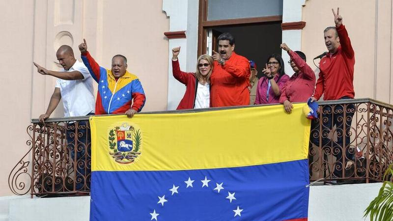 Nicolas Maduro (C) speaks to a crowd of supporters flanked by his wife Cilia Flores (2-L), Venezuelan Vice-president Delcy Rodriguez (R) and the head of Venezuela's Constituent Assembly Diosdado Cabello, among other supporters.