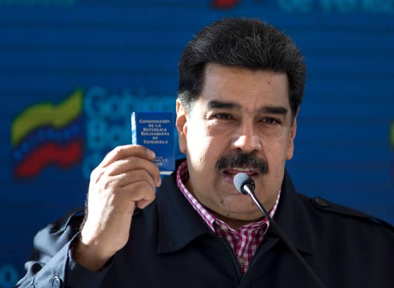 Venezuelan President Nicolas Maduro last month holding a copy of the Venezuelan Constitution, which most legal scholars say he'll violate tomorrow if he takes the oath for a new six-year term.