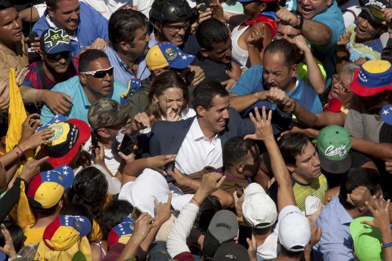 Venezuelan opposition leader Juan Guaido, center, greets supporters as he arrives at a demonstration demanding the resignation of President Nicolas Maduro, in Caracas, Venezuela, Saturday, Feb. 2, 2019.
