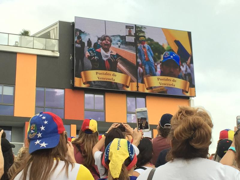 Venezuelan expats watch video of anti-government protesters in Caracas on Saturday at City Place in Doral.