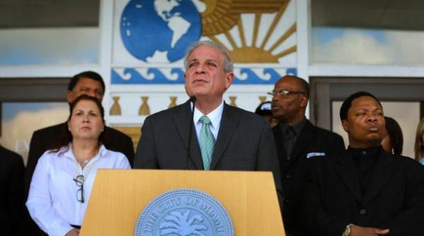 Miami Mayor Tomas Regalado surrounded by members of the community and other officials speaks to the media about gun violence on January 14, 2013 in Miami, Florida.