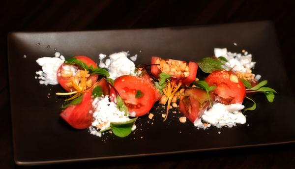 The popular Homestead tomatoes dish at Eating House also includes frozen coconut milk, peanuts, ginger, edible flowers, shoots and petals.