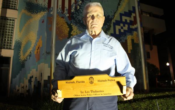Hialeah Police Lt. Leo Thalassites holds a plaque outside Hialeah City Hall after he was named the oldest active police officer in the country.