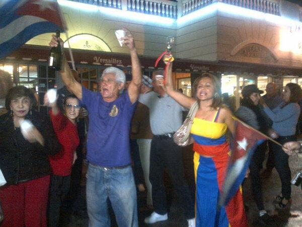Cubans and Venezuelans celebrate and pop champagne in front of Versailles.  They scream 'Viva Venezuela! Abajo Castro!'