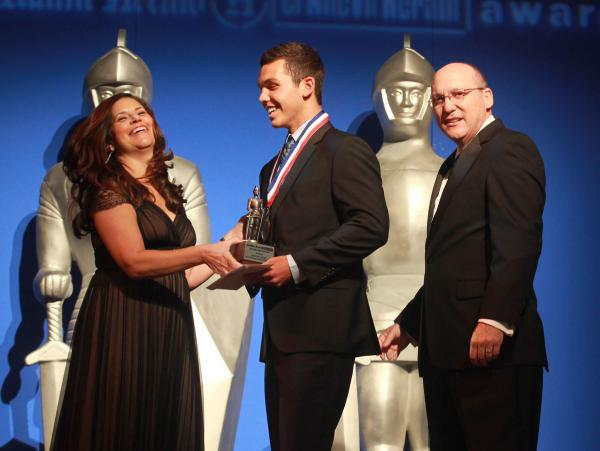 Aminda Marques Gonzalez (left), executive editor of The Miami Herald, and Manny Garcia (right), executive editor of El Nuevo Herald, present a Silver Knights award in business to Michael Jones from St. Thomas Aquinas High School in Broward County.