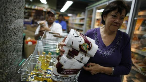A woman in Venezuela stocks up on toilet paper and other necessities.