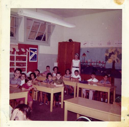 Tina Pinero stands with her second- or third-grade class of students circa 1964 or 1965. The students spoke Spanish as a first language. The classroom had no air conditioning.