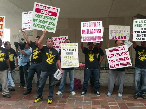 Protesting taxi cab drivers gather outside Government Center in downtown Miami.