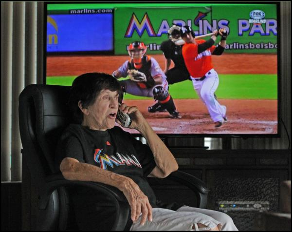 Eloise Card of Westwood Lakes watches a Marlins game and chats with her daughter Donna on the phone. The pair have watched every game together for the past four years.