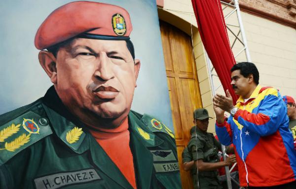 Venezuelan President Nicolas Maduro (right) next to an image of the late Hugo Chavez.