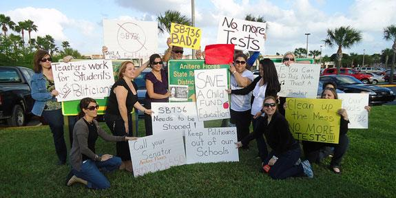 Teachers and police officers in Miami recently protest Gov. Rick Scott's budget cuts.