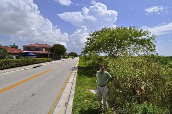 FIU Geography Professor Jeff Onsted straddles the Miami-Dade County Urban Development Boundary at Miller Road and SW 167th Avenue.
