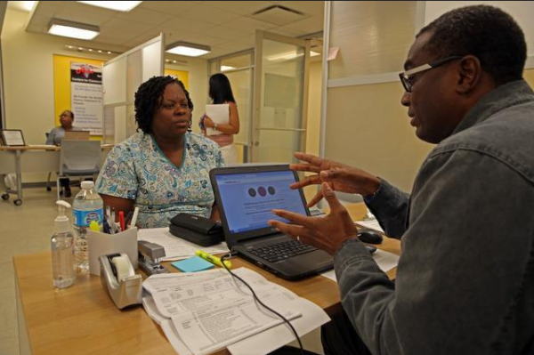 Marie Rachelle Dominique, 47, asks counselor Bernard Guiteau at the Borinquen Medical Center in Miami about signing up for health insurance.