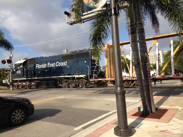 A Florida East Coast freight train runs through the middle of downtown West Palm Beach. South Florida's urban core developed around the FEC tracks. Now two projects hope to run passengers along the line for the first time in almost 50 years.