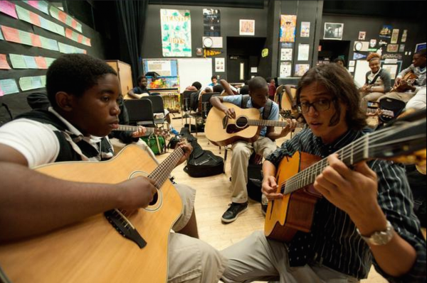 Leslie Augustin, 13, an eighth-grade student in the guitar class, gets individual attention from Jonathan De Leon, founder of the guitar program at the school.