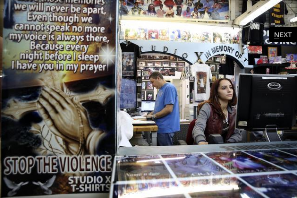 Hai Haliva, owner of Studio X, and Ayleen Lopez, a graphic designer, work inside the booth at the USA Flea Market, where they design R.I.P. t-shirts for customers. EMILY MICHOT / MIAMI HERALD STAFF