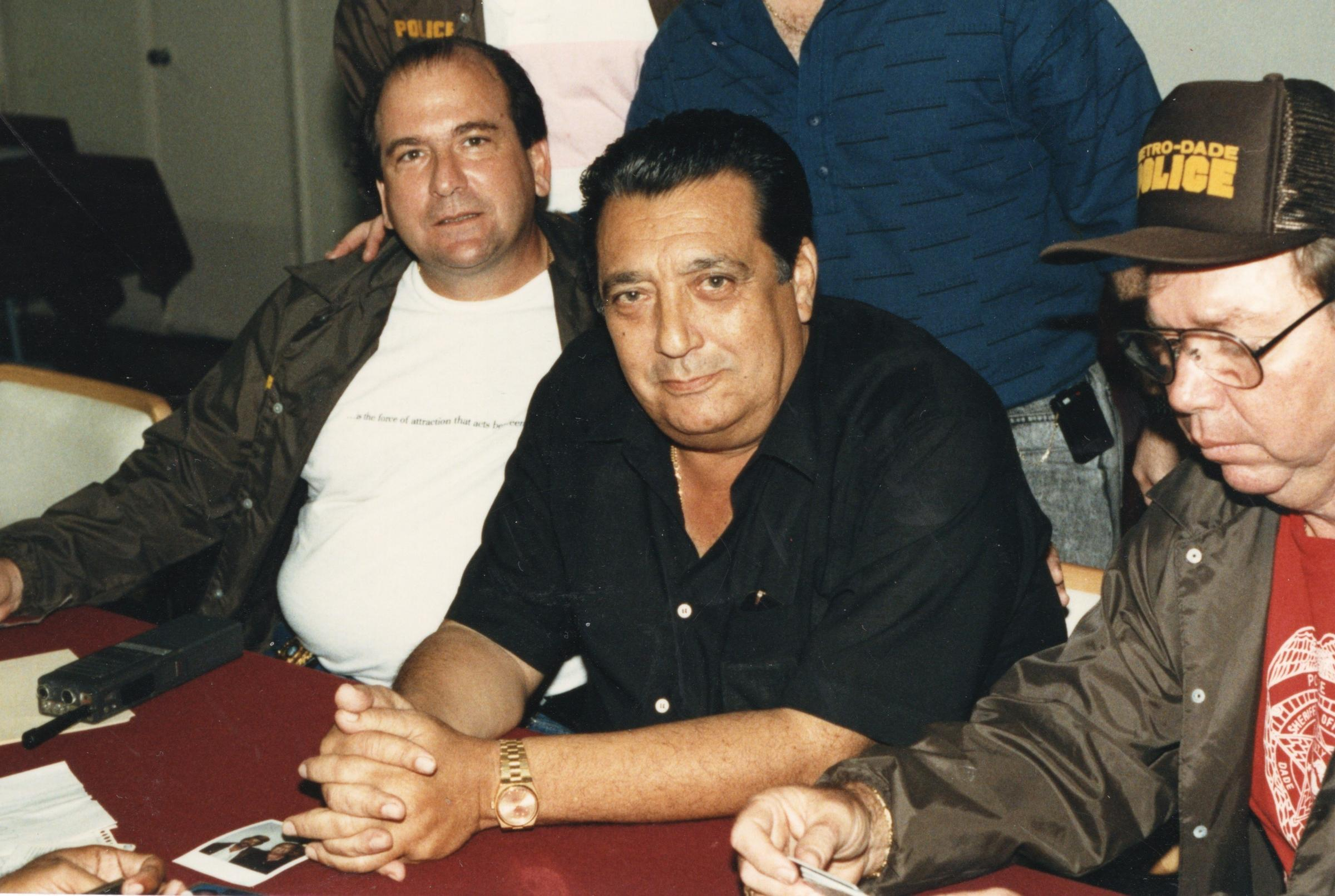 The late Corporation mob boss Jose Miguel Battle (center) surrounded by  Miami-Dade police after his 2004 arrest. (Battle died in prison in 2007, ...