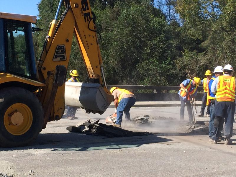 DOT workers repairing bridge approach damaged by October floods.