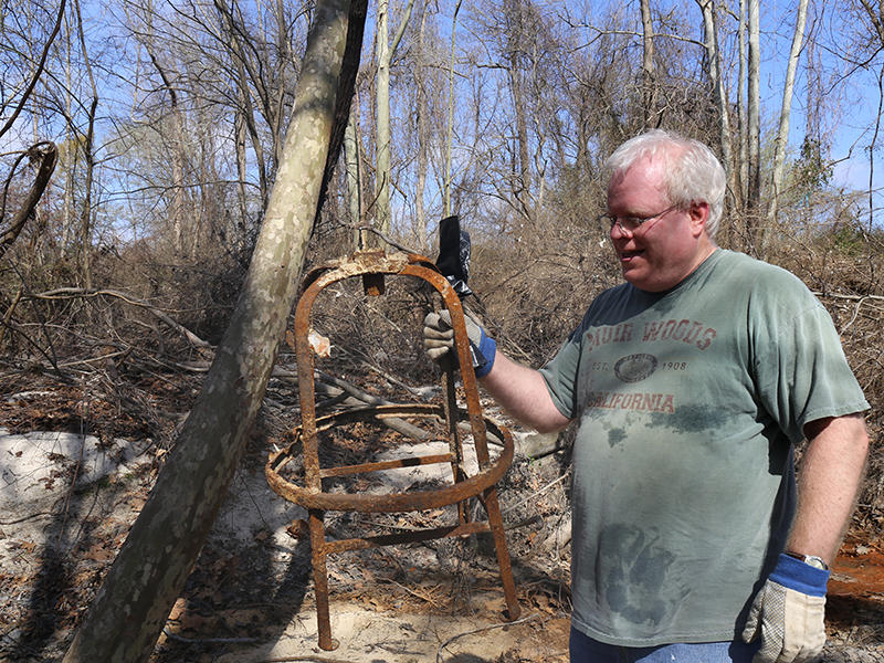 A clean-up volunteer holds what appears to be the base of a stool, found among the debris on Gills Creek.