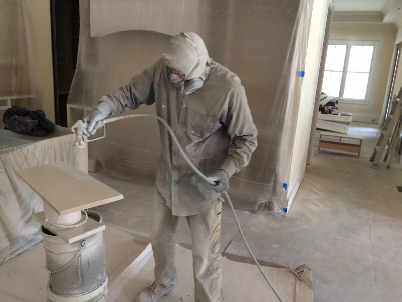 A worker spray paints a shelf as one of many repairs to the home of Rob and Lisa Echols of Columbia. Their home was flooded when the Semmes dam at Fort Jackson failed during the record-setting rains of early October, 2015.