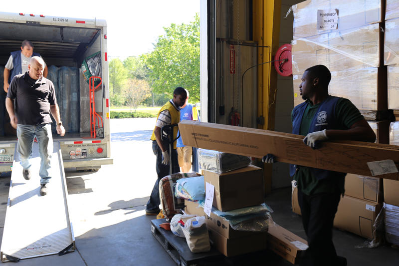 At the House in a Box warehouse, volunteers and grant-funded employees work together to serve flood-impacted families.