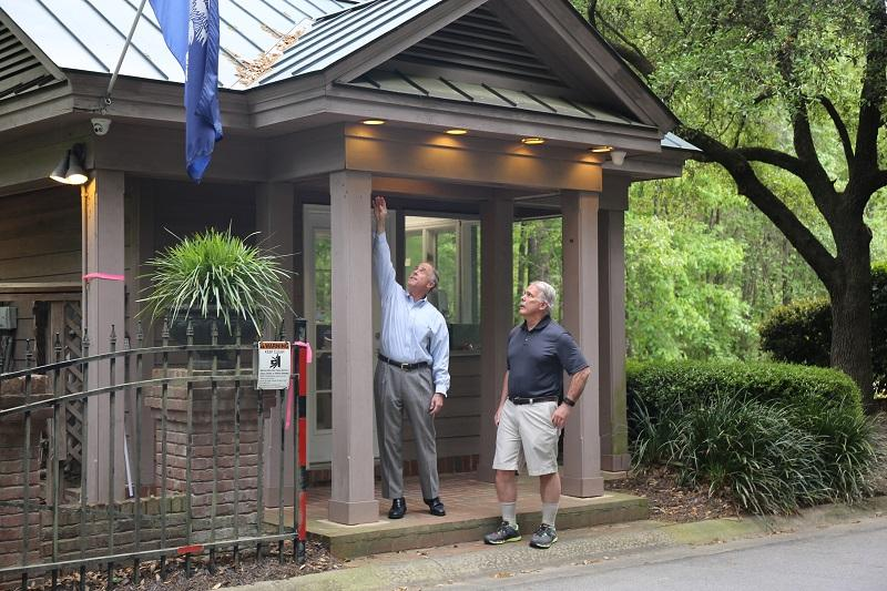 Dale Longacre reviews with neighbor Howard Bickley the height of the water on their neighborhood entrance booth as they perched atop a planter preparing to swim out against a strong tide that swept Bickley's car into deep water during October's flood.
