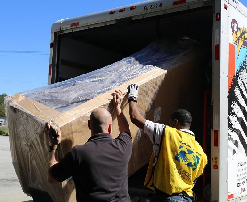 An House in a Box employee and a volunteer load a couch into a family's moving truck.