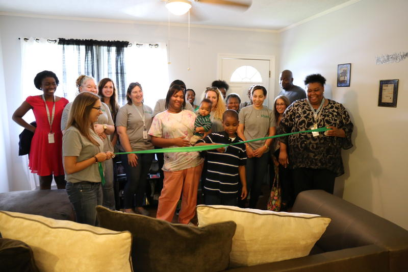 "Hearts and Hands Disaster Recovery staff join Keoashaws Brewer and her family for a ribbon cutting ceremony as part of their ""Welcome Home"" celebration."