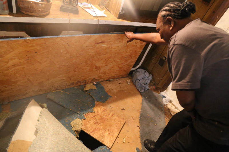 The floor of Harriet Mealing's trailer is riddled with holes. As a temporary fix, she has covered them with plywood.