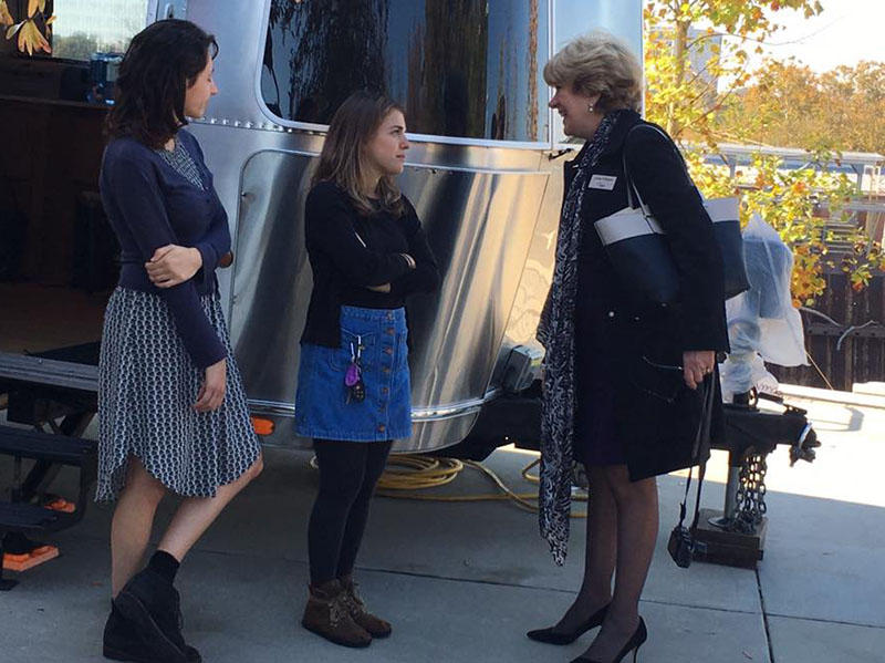 SCETV President and CEO Linda O'Bryon talks with two of StoryCorps facilitators outside the MobileBooth in Columbia.
