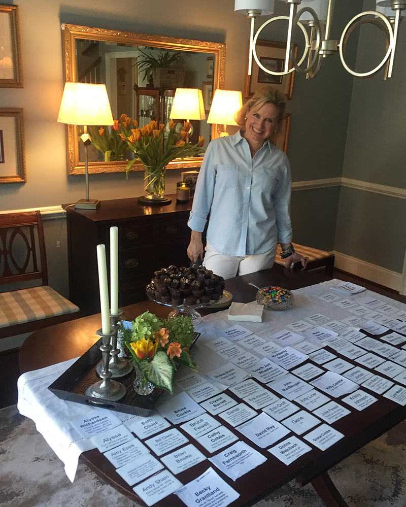 Tammy Moshier stands in her living room with nametags she made for the guests of her