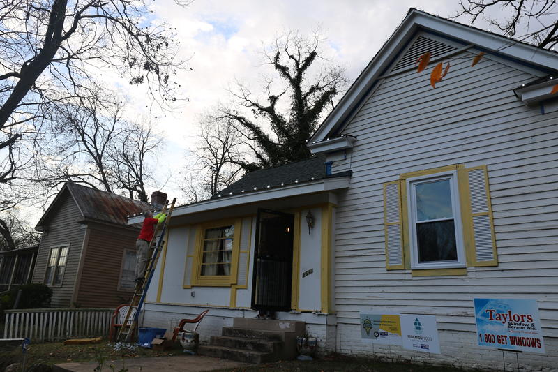 Illumineer worker installs Christmas lights on home of Columbia flood victim